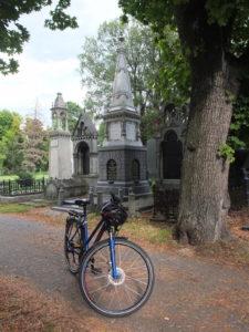 Bild eines Rades, dahinter Grabsteine