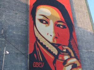 Bild eines riesigen Graffiti: Frau mit Spraydose